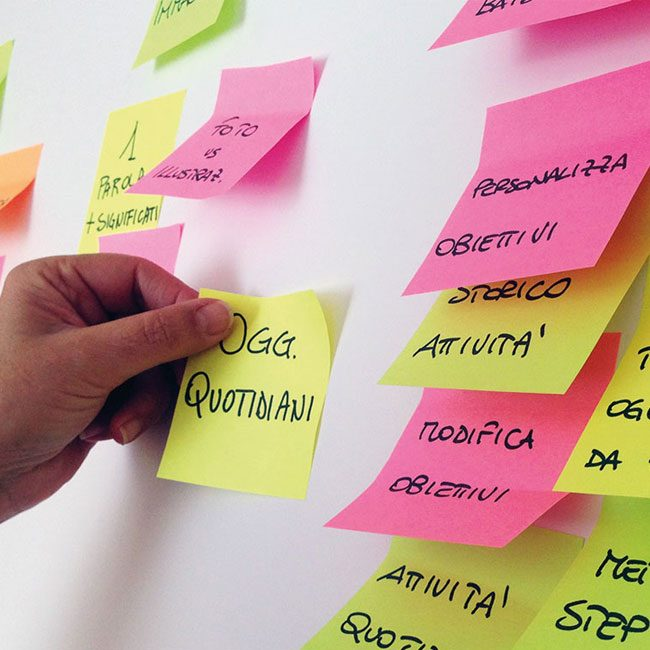 un utente sposta post it colorati appesi alla parete durante una focus group